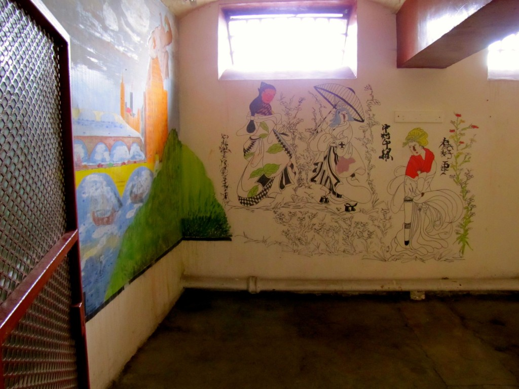 At some point, they knocked the wall out of between two cells to make a larger room for use as an art classroom. Some of the murals have been preserved.