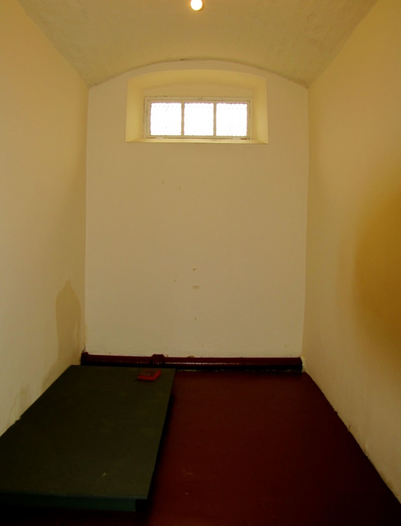 "This is a punishment cell. Note the absence of bedding - bedding was provided at night, but during the day, you could sit or lie only on the floor or on the wooden pallet. Thus, being sent to the punishment cell was called ""being on the boards."""