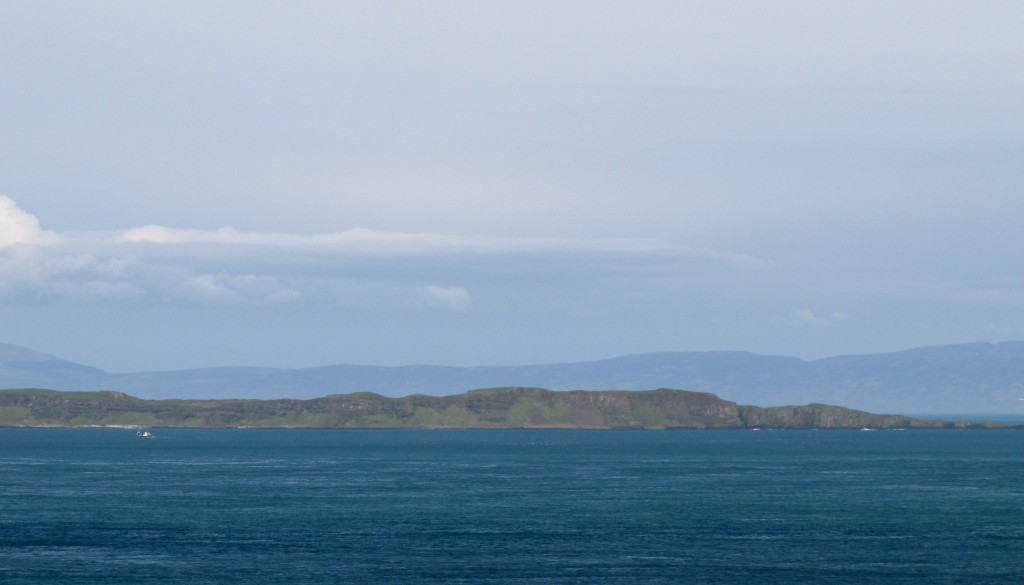 The island in the foreground is Rathlin Island. Interesting place. Behind it, the shadowy outline is the Mull of Kintyre - it's actually part of shoreline of Scotland, about twelve miles away.