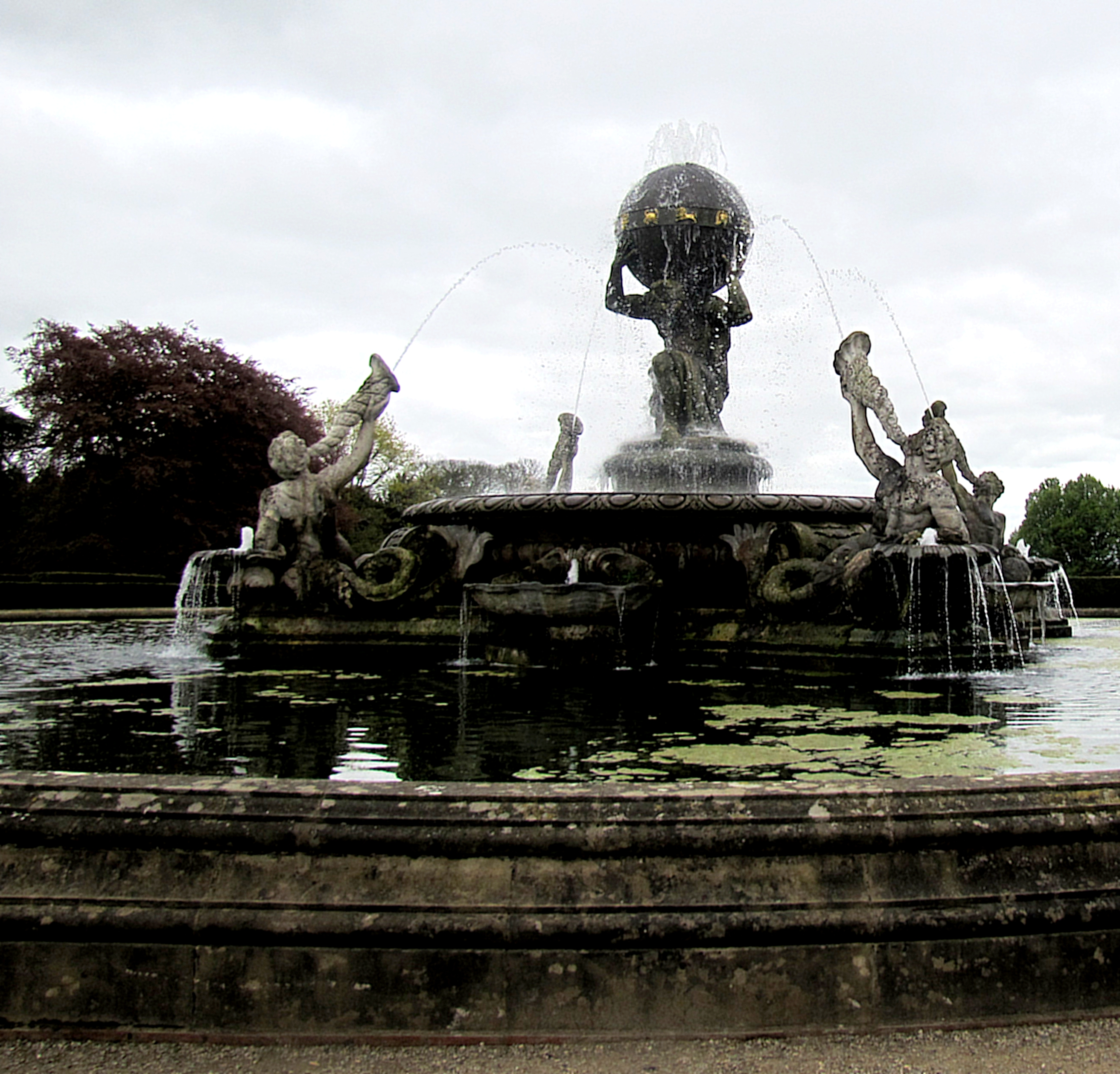 Atlas is in the centre, holding the world on his shoulders. Surrounding him are four tritons, spraying him with water. The tritons are about eight feet tall, so Atlas would be 10-11 feet tall if he were standing upright.