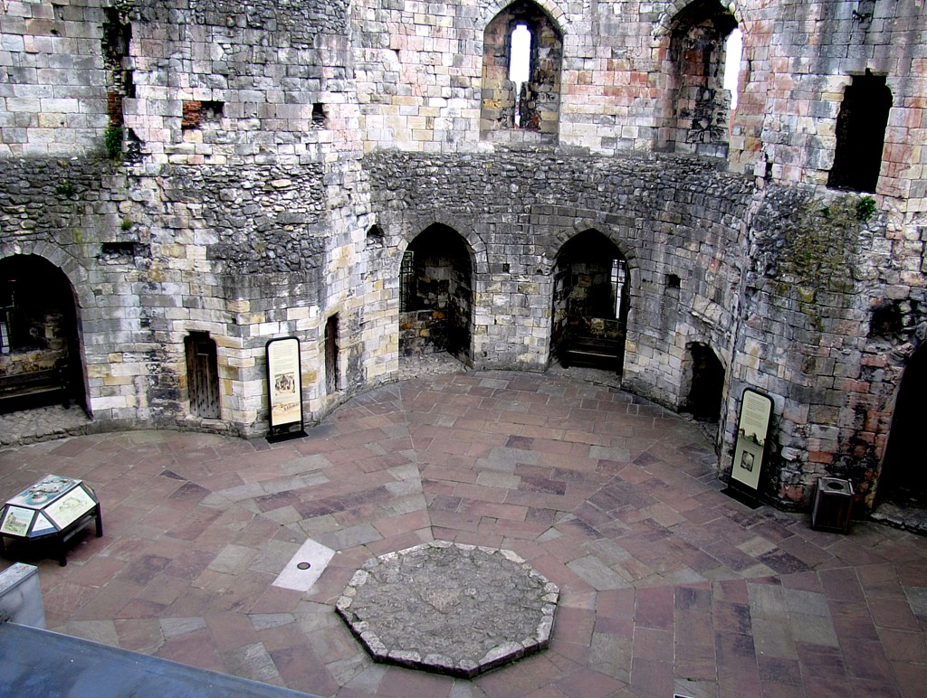This is the interior of Clifford's Tower. Back before the gun accident, there were wooden floors and partitions in here, turning it into an actual livable location. The large slab in the centre was the base of the central pillar that reached up to the former ceiling, providing support for the higher floors.