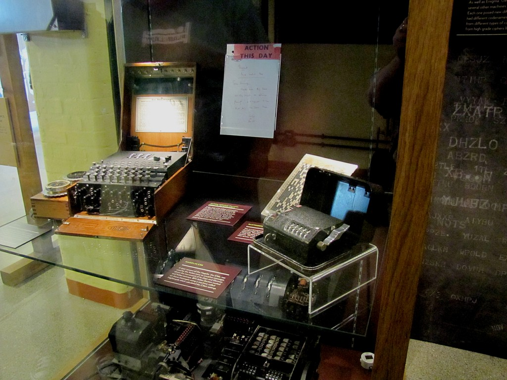 These are what it was all about. You've got an Enigma machine on the left, a much simpler Italian cipher machine on the right, and some pads above. The bottom shelf holds the much more complex Lorenz cipher machine.