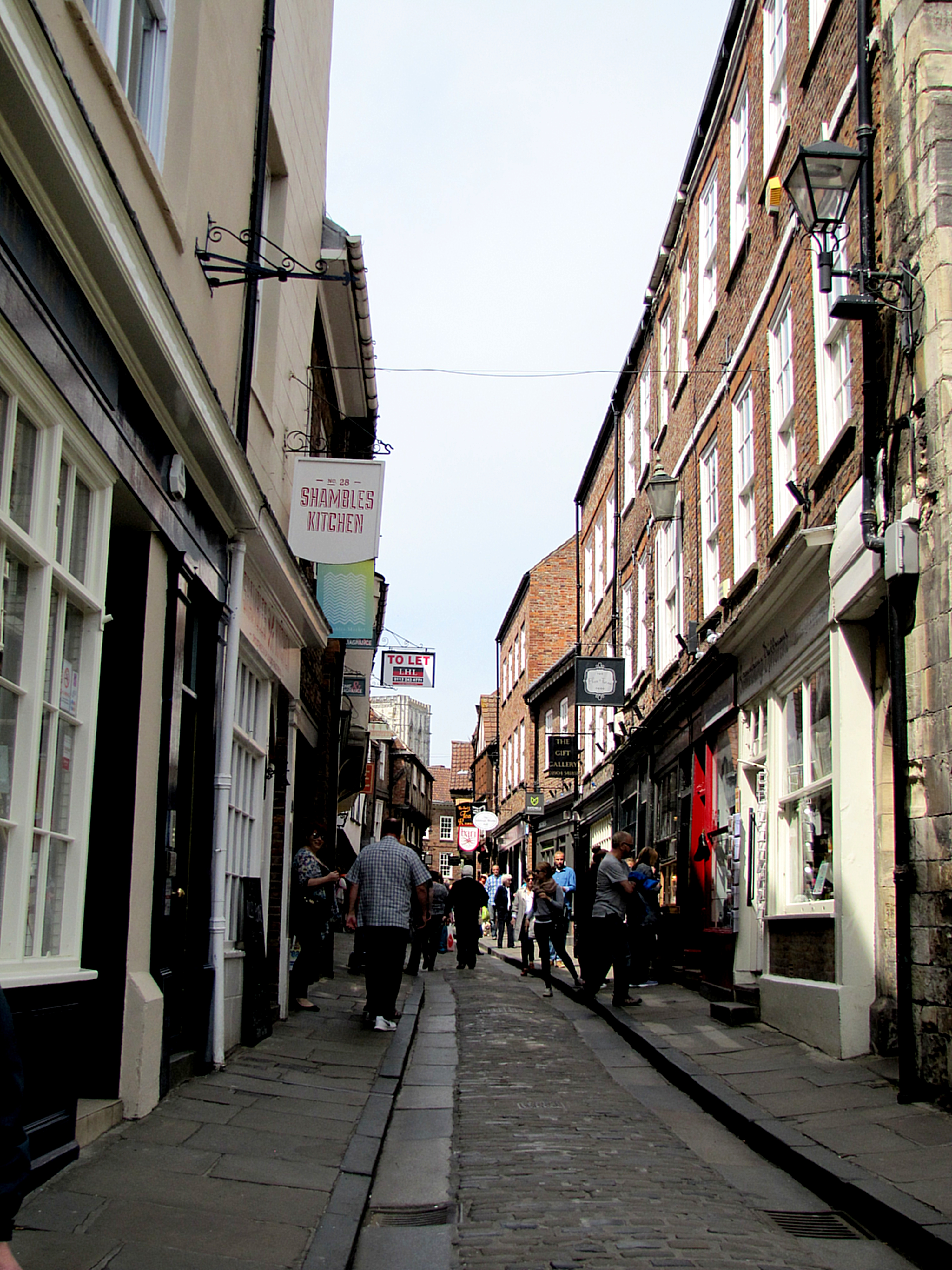 "Just in behind Whip-Ma-Whoip-Ma Gate is the Shambles. This is a medieval street, and used to be the street of butchers in York. The word comes from Fleshammels, an Anglo Saxon word meaning ""flesh shelves,"" referring to the display shelves in front of the shops. It's very narrow."