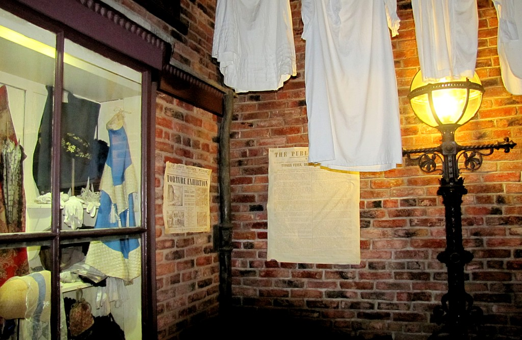 A little dead end alley, with washing hanging from the higher floors. The two posted papers are a notice about how to avoid disease from city water, and an advertisement for an exhibition of torture implements and accounts.