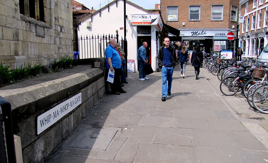 "This is Whip-Ma-Whop-Ma Gate, said to be the shortest street in York. It runs from where I'm standing to the Mali salon you see at the end. The numbers on the street are 1, 1B, and 1 1/2. It doesn't reach 2. The name is said to be a corruption of a Danish Viking phrase that means ""neither one thing nor another."""
